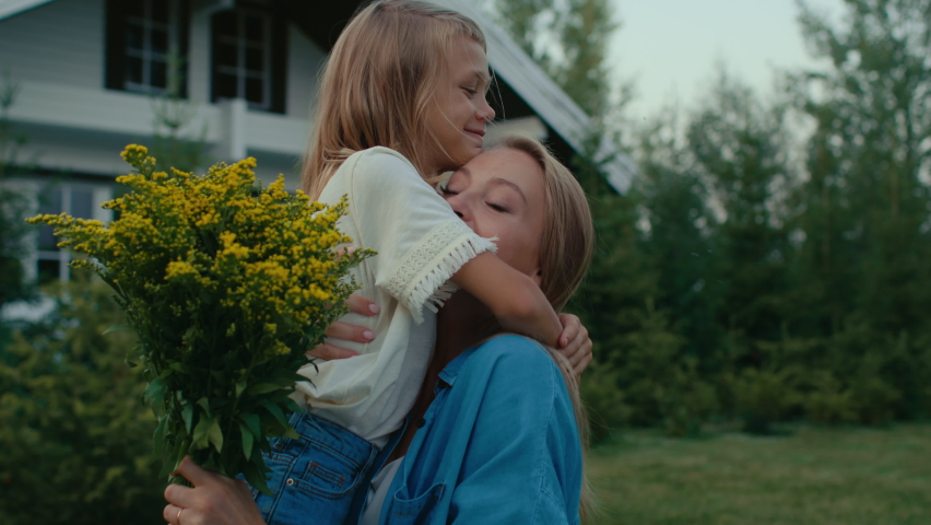 Family of happy mom and little girl spending time outside near house. Small child gives meadow flowers to pretty mother at front yard. Woman takes bouquet of wildflowers and looks at it with joy