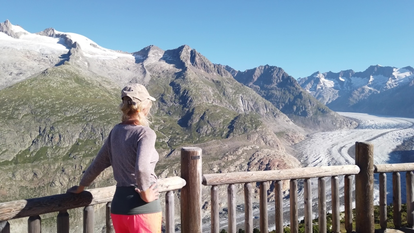 Woman looking at Alpine Glacier from Moosfluh viewpoint, Valais Canton, Switzerland, Europe. Sitting tourist woman looking the Alpine glacier. Outdoor activities. Trekking in Swiss Alps in summer | Shutterstock HD Video #1059662051