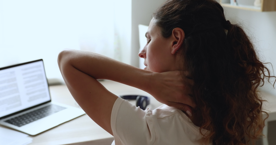 Close up rear back view woman sit at workplace experiences severe pain in neck, rubbing it to relieve muscle tension. Cervical osteochondrosis, tired overworked female, sedentary lifestyle concept