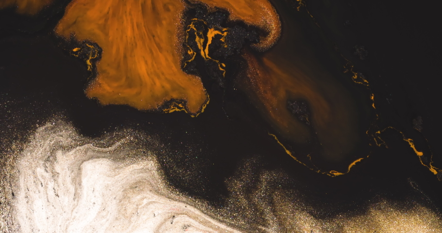Luxurious Pale Gold glitter moving in orange and black background.  Feels sophisticated and retro, vintage. Abstract macro liquid art.
