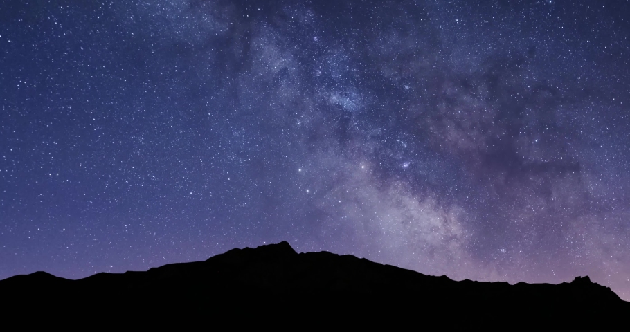 The Milky Way Galaxy moving over the mountain ridge. Night lapse from night to day. Starry night.