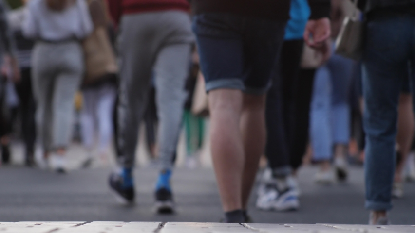 Crowd of pedestrians crossing a city street. No logos or faces visible. Low angle view of legs and feet of people. A lot of people are crossing the street. Society and city life concept. Feet closeup Royalty-Free Stock Footage #1059688316