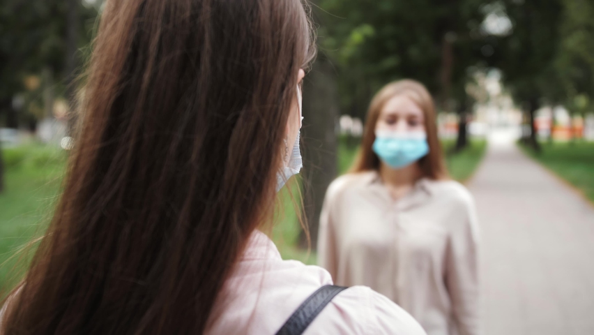 Students in protective medical mask greet each other elbows during pandemic of coronavirus. Avoid handshakes and hug due to pandemic. Royalty-Free Stock Footage #1059689672