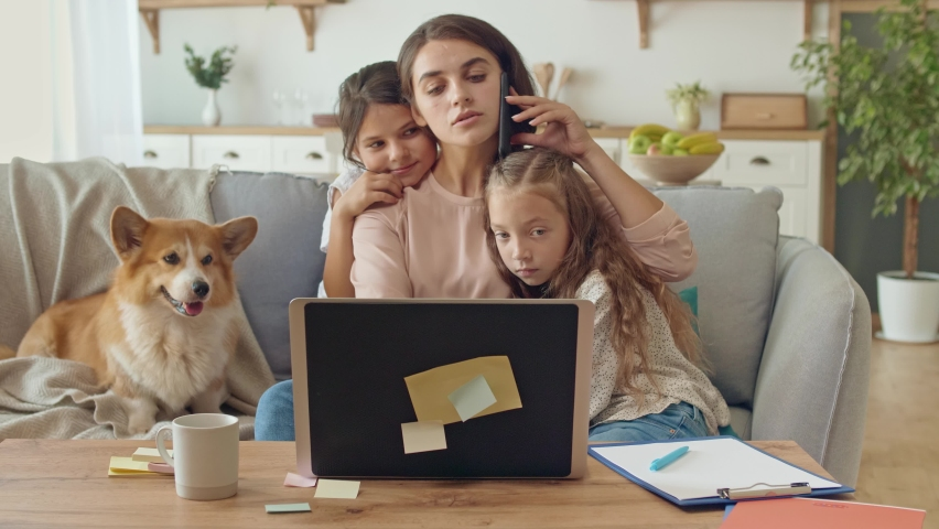 Lovely Mother Working Remotely From Home While Hugging Kids. Mother is Stroking a Daughters.A Busy Mother Working Remotely With a Laptop and Doing Business Conversation on the Phone Sitting on a Couch Royalty-Free Stock Footage #1059692120