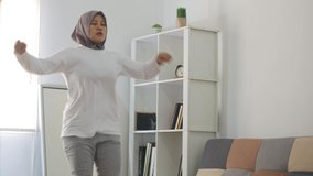 Asian muslim woman wearing hijab doing exercise at home while watching online video instruction on laptop, indoor home workout concept, keep healthy on new normal lifestyle, knee raises