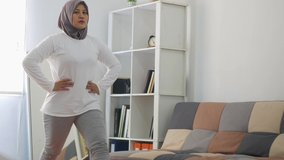 Asian muslim woman wearing hijab doing exercise at home while watching online video instruction on laptop, indoor home workout concept, keep healthy on new normal lifestyle, lunges