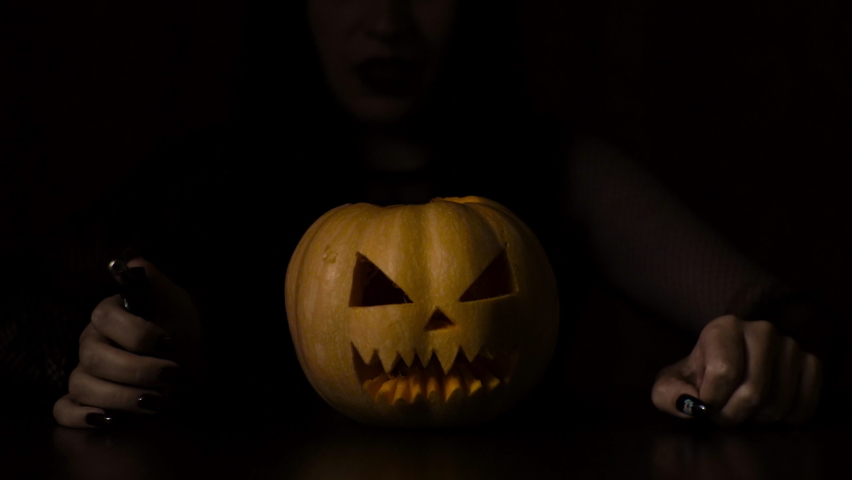 A young girl lights a candle in a pumpkin. Halloween holiday Isolated black background.   Shutterstock HD Video #1059697184