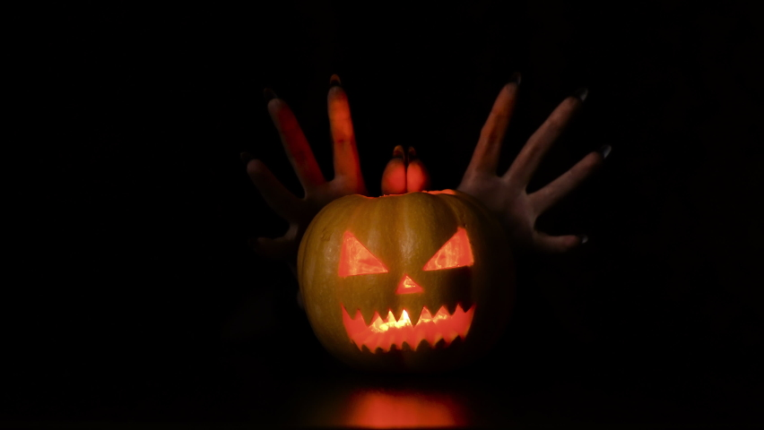 Young woman fooling around with a pumpkin. Halloween holiday. Gives creepy horns. Isolated black background.   Shutterstock HD Video #1059697193