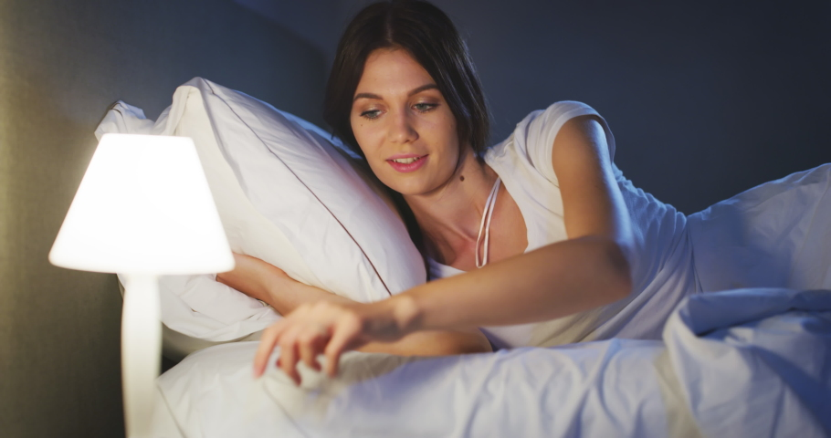 An young brunette woman is switching off the light and going to sleep peacefully under warm duvet blanket in a cosy bed in a bedroom.Concept of comfort Royalty-Free Stock Footage #1059709646