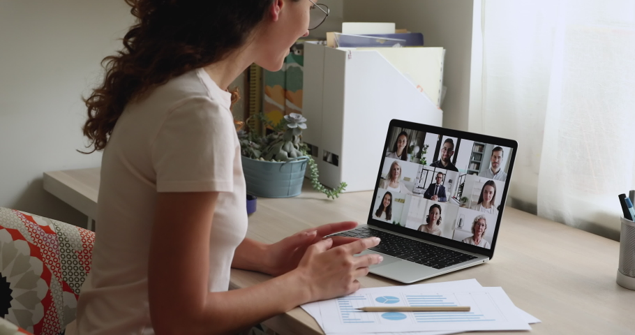 Diverse team participate in group videocall, woman sit at workplace desk greeting colleagues start virtual meeting solve current business issues using modern technology and videoconference app concept Royalty-Free Stock Footage #1059716333