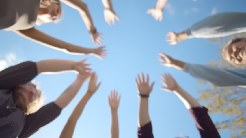 Bottom view of young diverse people putting their hands together outdoors. Friends with stack of hands showing unity and teamwork. Students standing in circle putting hands together | Shutterstock HD Video #1059718904