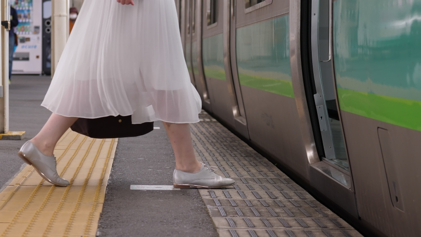 Passenger lady board on rapid transit train, low half shot of legs. Blurred background, few people walk at distance on rather empty platform at terminal station Royalty-Free Stock Footage #1059721940