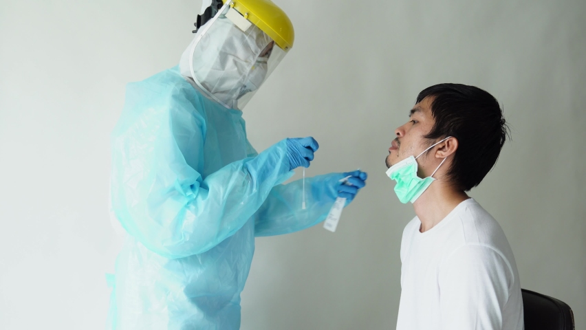 The doctors in the PPE protective suit performed a nasal congestion swab covid from a person to test for the coronavirus covid-19 infection. Swab Corona test - Corona virus / Covid-19 Royalty-Free Stock Footage #1059721946