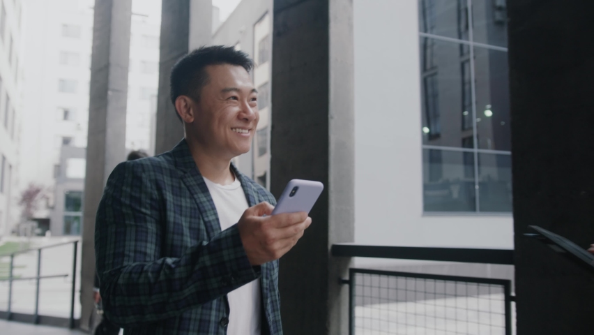Happy asian young entrepreneur browsing mobile phone internet during office break walking along business district. Successful businessman going to work. Royalty-Free Stock Footage #1059722369