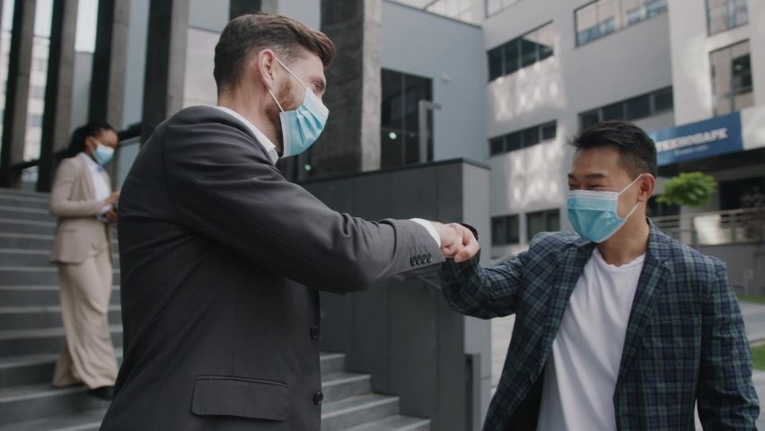 Two businessmen in medical mask meet each other and go to work together in modern office building. Quarantine successful respiratory protection manager coronavirus. Slow motion Royalty-Free Stock Footage #1059722414