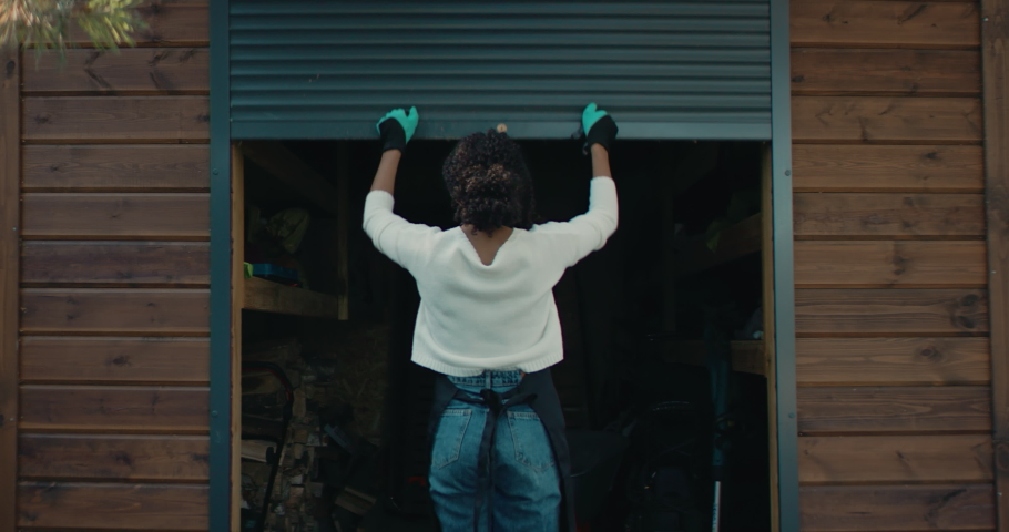 Young adult Black female opens shed door, picking gardening instruments inside. Shot on RED Cinema camera with 2x Anamorphic lens