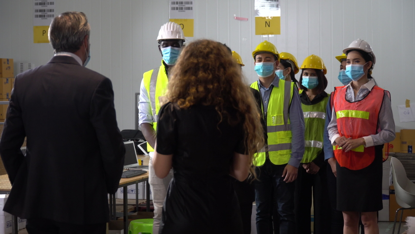 Executive business man and manager wearing face protective medical mask meeting in large warehouse explain new normal policy protect coronavirus or covid-19 outbreak pandemic   . Owner visits factory Royalty-Free Stock Footage #1059725471