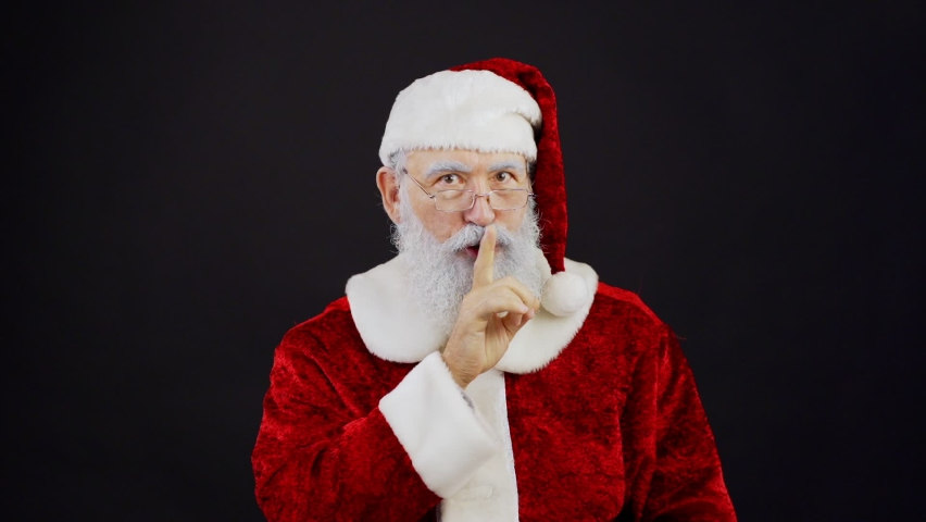 Waist up portrait of Santa Claus in traditional red costume and eyeglasses looking at camera, doing shh gesture, winking and smiling in slow motion standing against black background | Shutterstock HD Video #1059726644