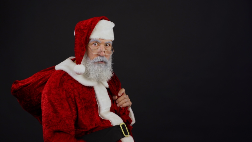 Medium shot of Santa Claus with Christmas sack walking into frame, showing you shh gesture and tiptoeing away trying to be unnoticed | Shutterstock HD Video #1059726764