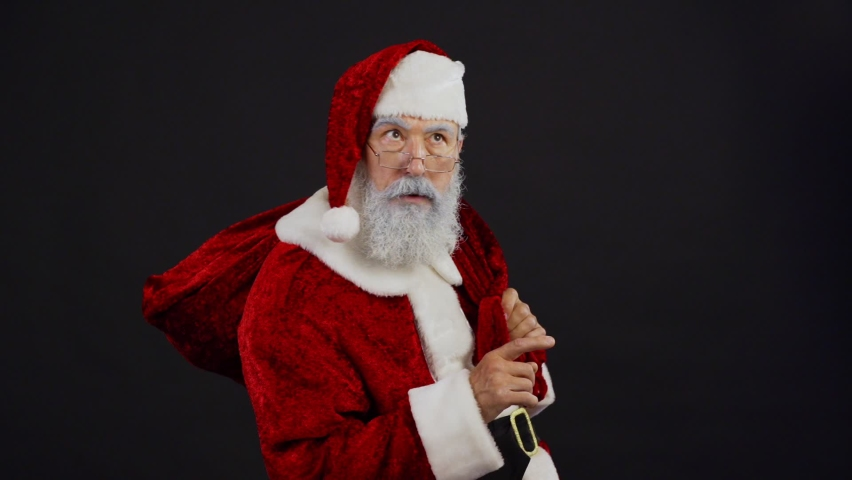 Medium shot of Santa Claus with Christmas sack walking into frame in slow motion against black background, showing you shh gesture and tiptoeing away trying to be unnoticed | Shutterstock HD Video #1059727046