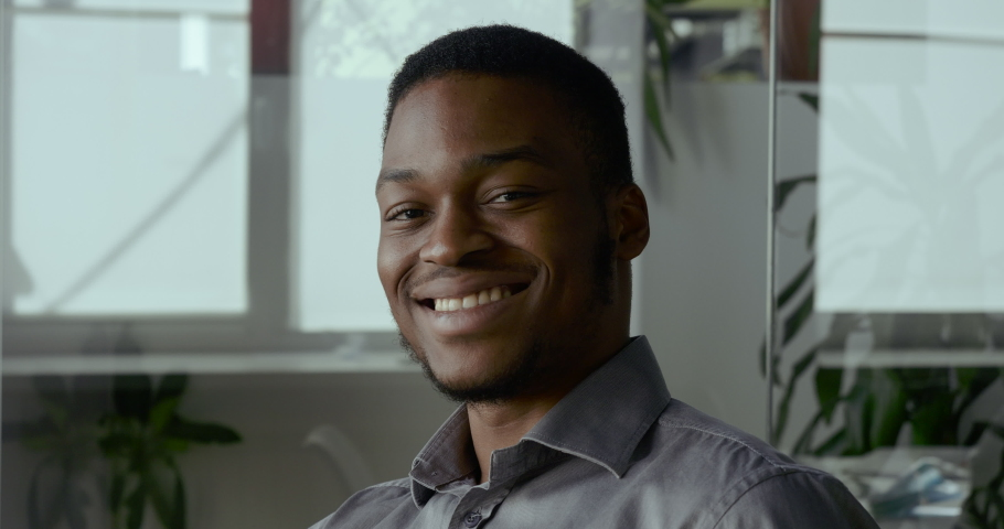 Smiling african american millennial professional man looking at camera. Happy confident handsome smart young adult entrepreneur, leader, manager posing in office. Close up face view business portrait