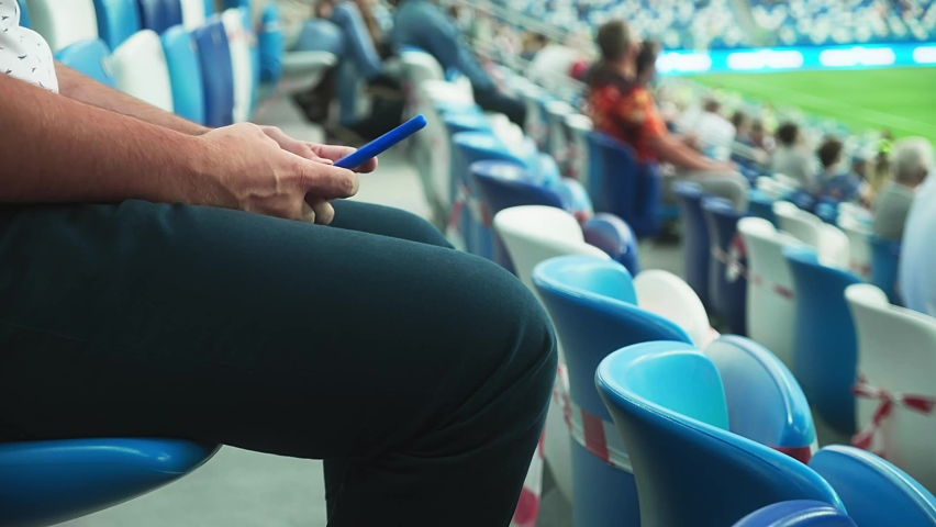 A man sits on the stadium stand and surfing social media on his smart phone during a football or soccer match. Mass event during coronavirus quarantine. Close-up of hands. High quality 4k footage Royalty-Free Stock Footage #1059734240