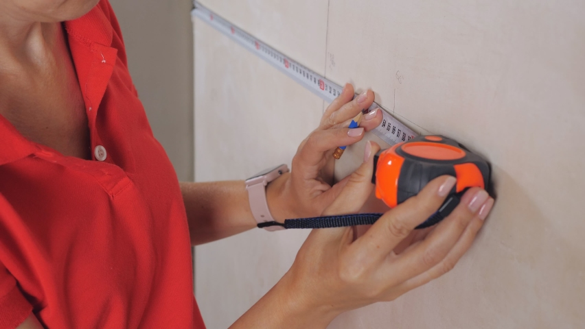 Women's hands measuring plaster wall for further wallpapering. | Shutterstock HD Video #1059740267