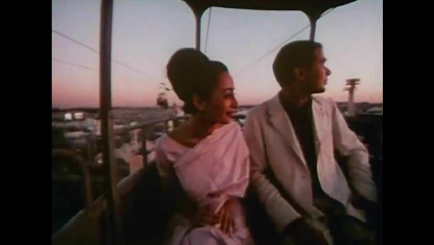 CIRCA 1960s - An Indian couple rides a sky tram at dusk at the 1964 New York World's Fair.