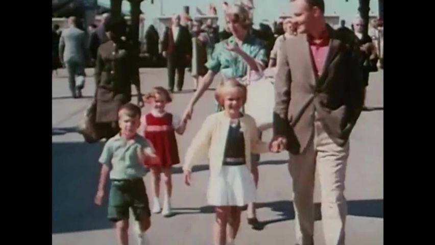 CIRCA 1960s - Dozens of people pour into the entrance of the New York World's Fair, including families, a boy scout troop, and teachers in 1964.