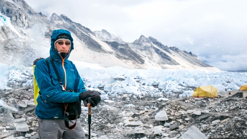 Young man in blue jacket resting after climbing. Mountains and tourist tents in the background. Trekking in Nepal, Everest Base Camp. Snow falling. Travel sport lifestyle background. Slow motion 4K