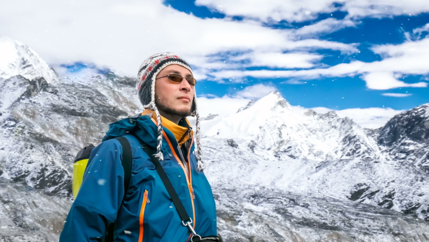 Portrait of young man in blue jacket resting after climbing. Mountains and cloudy blue sky in the background. Trekking in Nepal, Everest Base Camp. Snow falling. Lifestyle background. Slow motion 4K