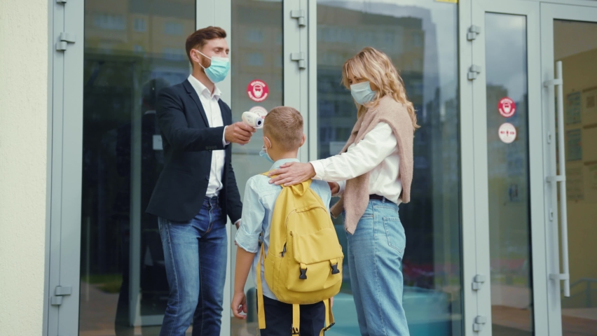 Security guard at school checking temperature of young junior student. Beautiful mom accompanies her son to the school building. Face masks. Virus prevention. Royalty-Free Stock Footage #1059752540