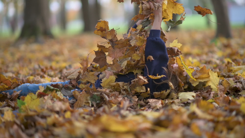 A funny girl lies on fallen leaves and throws the leaves up. Children in autumn park