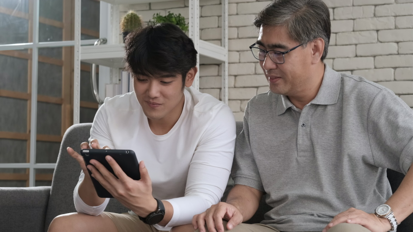 Happy two age generations asian men family old father embracing young adult son having fun enjoying using digital tablet watching funny social media video using mobile apps at home sit on sofa. | Shutterstock HD Video #1059763358