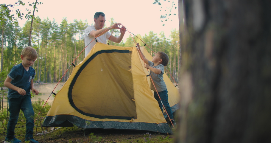The children, together with their father, set up a tent for the night and camping in the forest during the journey. A man and two children 3-5 years old together in a hike gather a tent in slow motion