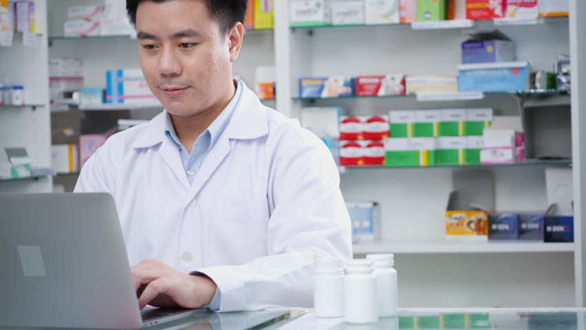 Doctor man working in pharmacy store at hospital. Asian pharmacist male looking laptop computer checking medication details in pharmacy drugstore. Concept of medical technology, business, lifestyle. | Shutterstock HD Video #1059769715