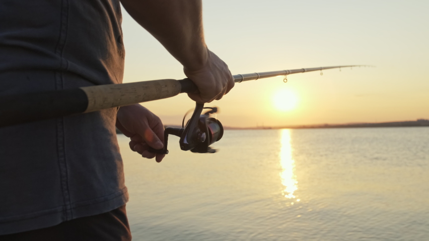 Handle rotation with reel of fishing rod against of orange sunset slow motion. Man hobby fishing on sea tightens a fishing line reel of fish summer. Lens flare. Calm surface sea. Bright disk of sun Royalty-Free Stock Footage #1059773018