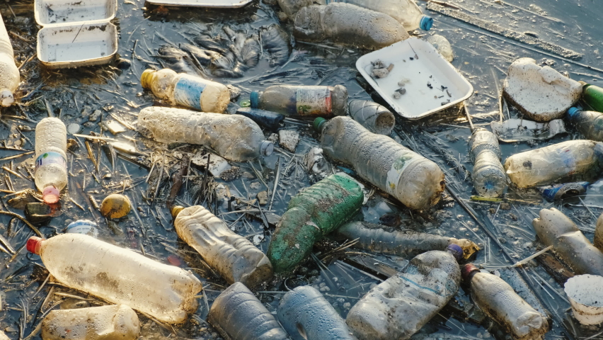 Plastic bottles in sea. Plastic bags. Garbage. Ecological catastrophe, save the planet. Blue calm sea water. Trash.  Floating rubbish floats in the sea. Construction ladle Royalty-Free Stock Footage #1059773027
