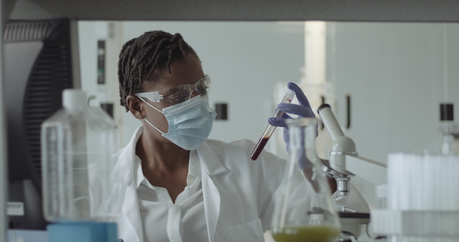 Black Female Laboratory Scientist Conducts Experiment in Science lab looking at blood sample with Coronavirus Royalty-Free Stock Footage #1059779771