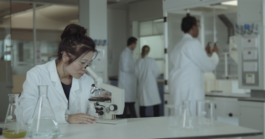 Asian Female Laboratory Scientist Conducts Experiment in Science lab looking at microscope in busy lab, diversity Royalty-Free Stock Footage #1059779843
