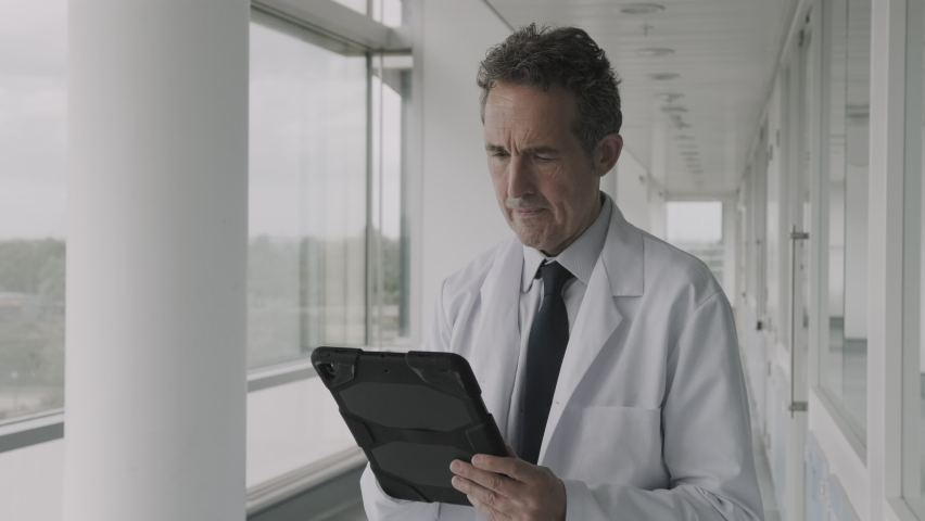 Mature Male Doctor standing in modern hospital corridor working on digital tablet and looking into hospital ward Royalty-Free Stock Footage #1059779852