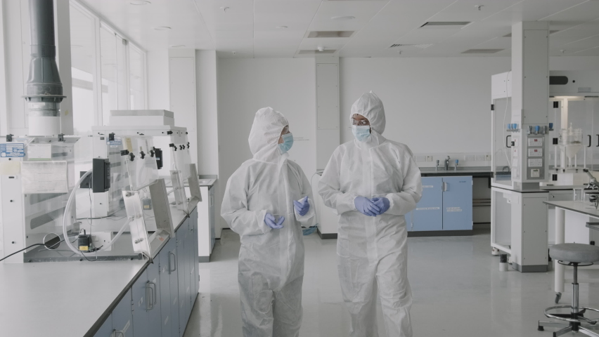 Two Scientist walking in laboratory wearing protective coverall discussing science experiment test results Royalty-Free Stock Footage #1059779864