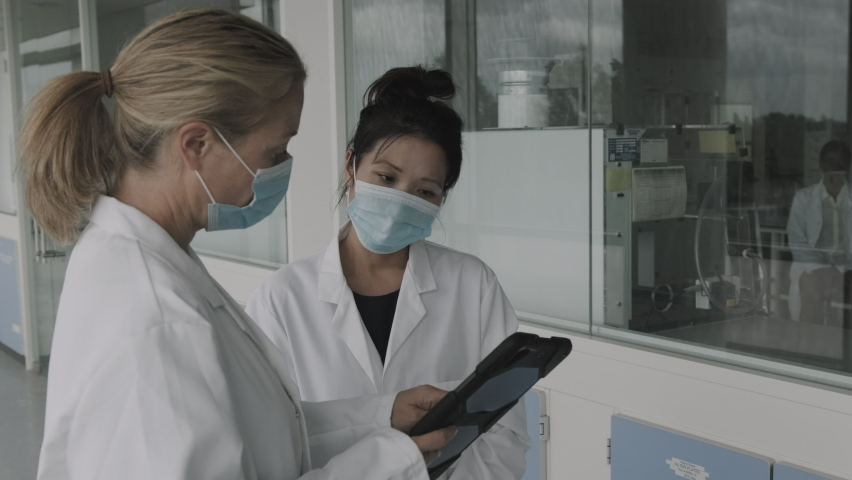 Female doctors meeting in hospital corridor discussing test results on digital tablet computer technology, wearing surgical face mask during Coronavirus pandemic Royalty-Free Stock Footage #1059779927