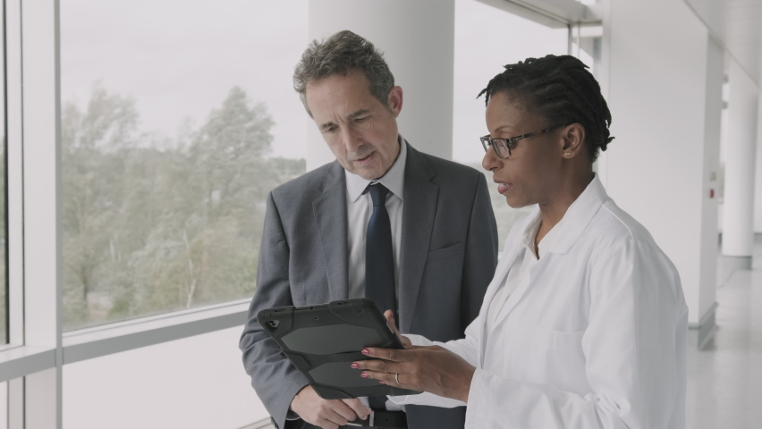 Doctors meeting in hospital corridor discussing test results on digital tablet computer technology | Shutterstock HD Video #1059779936