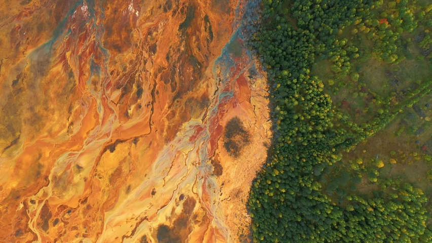 Lifeless orange toxic lake near green trees. Industrial plant pollutes soil and forest. Concept of environmental disaster and habitat destruction. Aerial view, drone flying | Shutterstock HD Video #1059783950