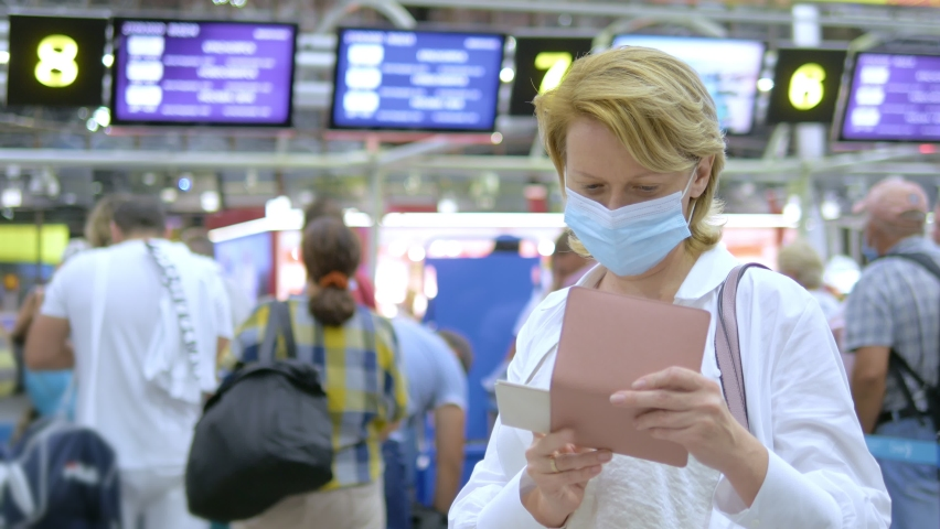 Close-up. masked woman with passport and boarding pass at the airport.
