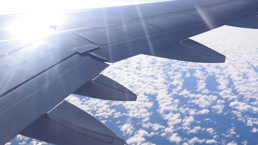 Passenger plane flying above the clouds. View from the wing of the plane. Travel concept