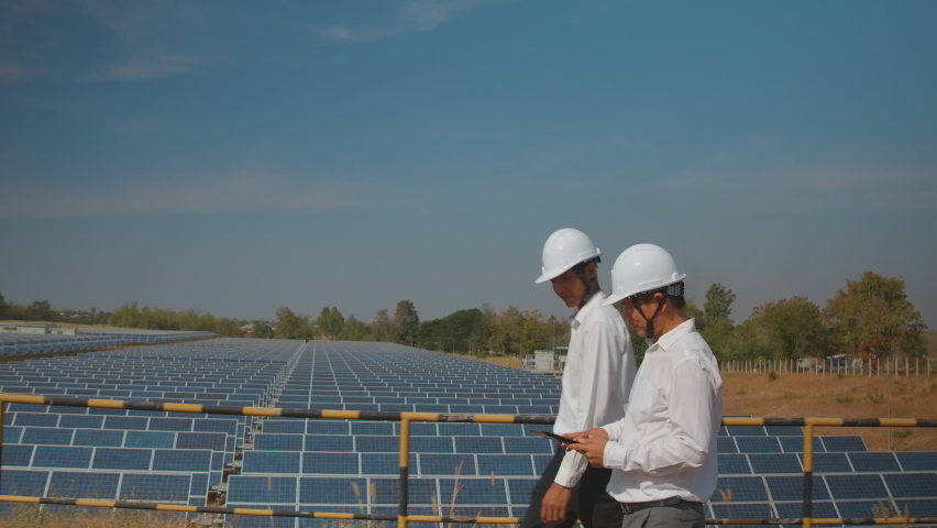 Technician and investor walking in Solar cell Farm through field of solar panels checking the panels at solar energy installation.Solar cells will be an important renewable energy of the future. | Shutterstock HD Video #1059801152