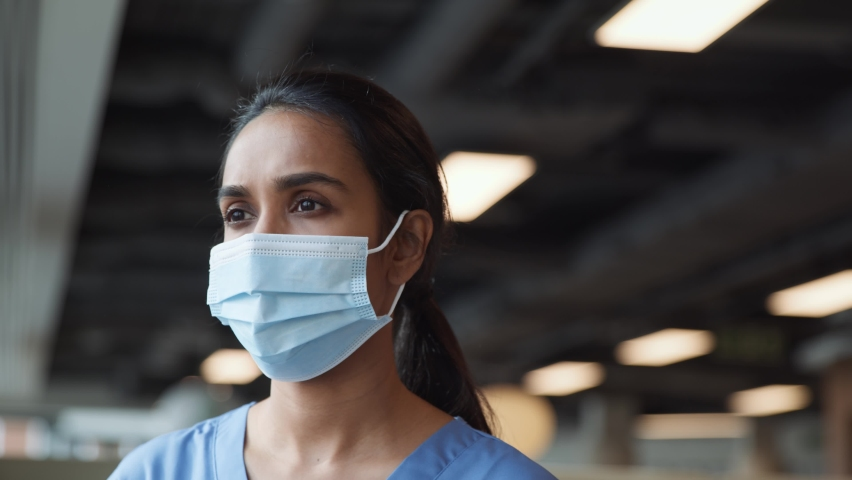 Portrait of smiling overworked nurse in scrubs taking off face mask during break in busy hospital during health pandemic - shot in slow motion