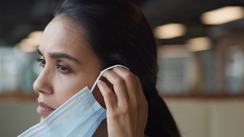 Portrait of overworked nurse in scrubs putting on face mask after break in busy hospital during health pandemic - shot in slow motion   Shutterstock HD Video #1059802049